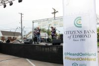 "Citizens Bank of Edmond President and CEO Jill Castilla takes to the mike during the bank's ""Heard On Hurd"" concert and street festival. Social media makes the core of the bank's promotion of the event."